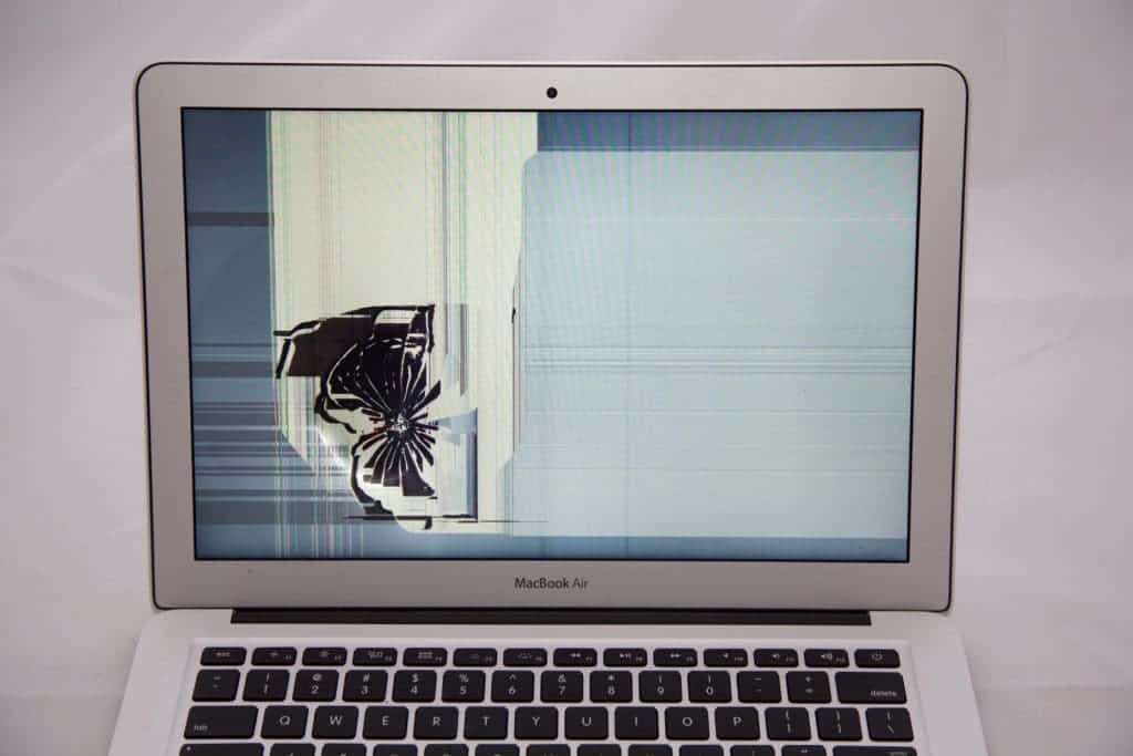 impact damaged MacBook Air Screen with Crack starting on the left side centered from a hard impact radiating outward.