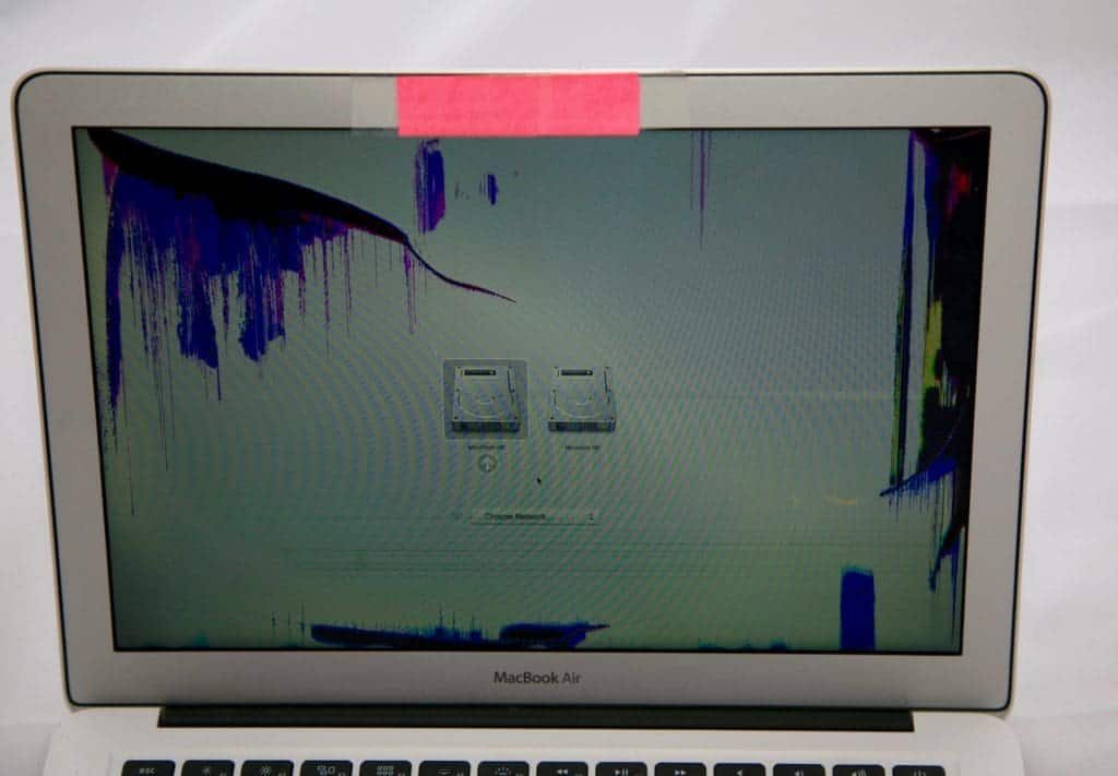 "13"" MacBook Air with red sticky note covering the isight camera. Display is damaged causing purple discoloration in the top left and far right of the dispaly"