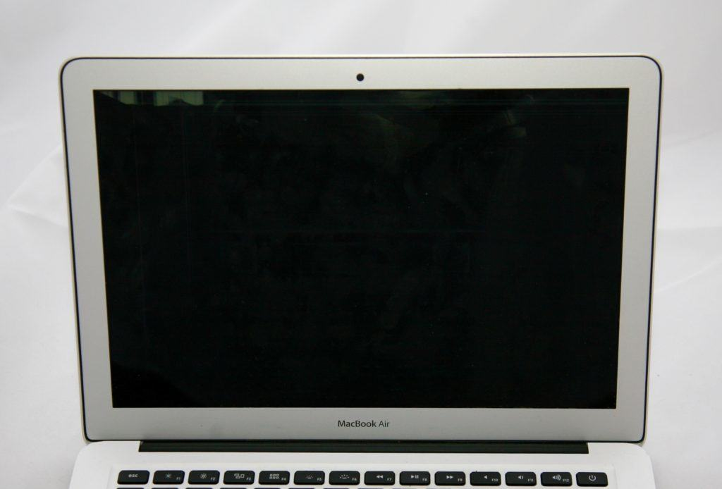 "13"" MacBook Air with almost complexly black screen. The only visible part of the display is the very top left."