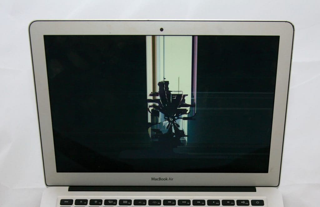 13 Inch MacBook Air with a spiderweb crack from impact to the apple logo on the back of the display.