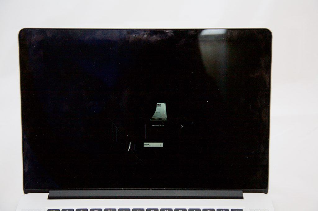 MacBook Pro Retina with half of the startup drive visible. The other half is blacked out by the crack on the screen